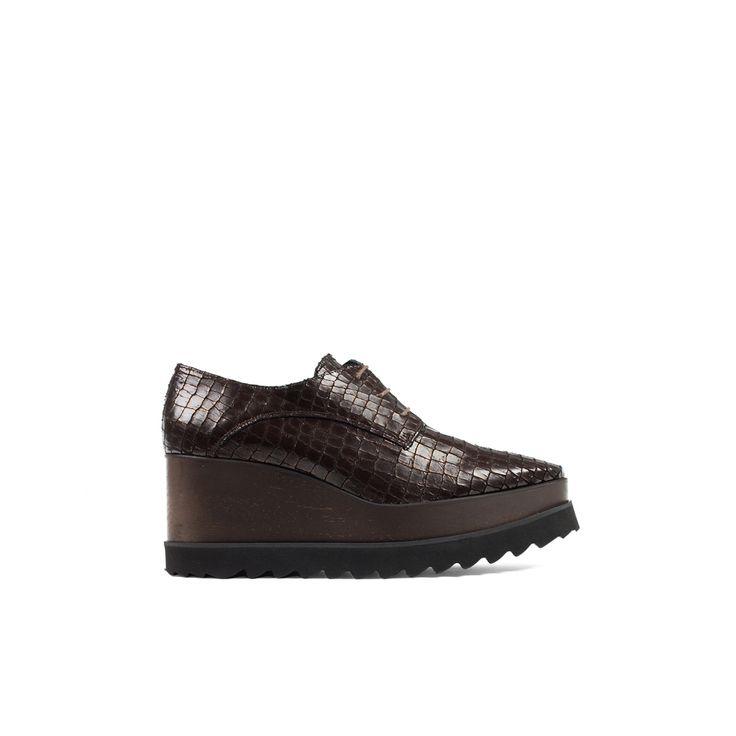Zapato Oxford realizado en piel de acabado texturizado con cierre de cordones. Tacón tipo cuña de madera, con suela dentada de goma para mayor comodidad. Edición única y renovada de uno de los zapatos clásicos de Un Paso Más.