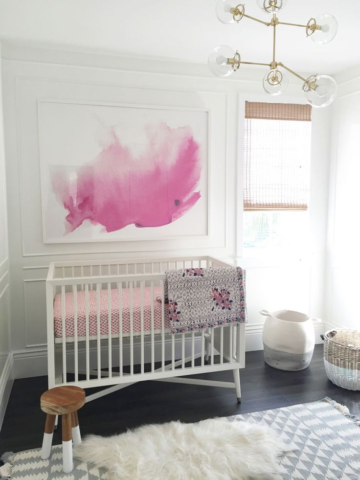 modern and simple nursery with bold watercolor artwork, neutral pinks, and textured grey textiles