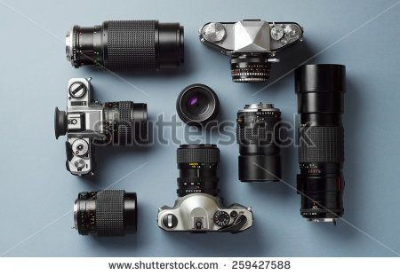 Collection of vintage cameras and camera lens well organized over blue background, top view