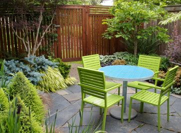 This tiny courtyard is a perfect outdoor dining spot. It is just outside the kitchen and has the perfect amount of room for a custom metal bistro table and four chairs. The tightly-laid flagstone is a perfect floor, and the narrow, but rich planting beds give the space warmth and additonal depth. A redwood fence balances privacy with light and airflow that keep the plants happy and make the garden feel more spacious. See more of our work at mosaic-gardens.com.