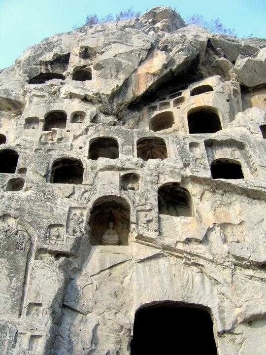 """China - The Longmen Grottoes or Longmen Caves are one of the finest examples of Chinese Buddhist art. There are as many as 100,000 statues within the 1,400 caves, ranging from an 1 inch (25 mm) to 57 feet (17 m) in height. The area also contains nearly 2,500 stelae and inscriptions, whence the name """"Forest of Ancient Stelae, as well as over sixty Buddhist pagodas. #RTW #travel www.goachi.com"""