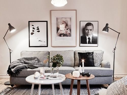 Living room - mix of gray sofa with framed photos w/gold frames, black frames, white coffee table
