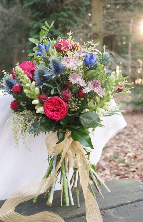 Vibrant, naturalistic and colourful hand-tied bridal bouquet. This bouquet has red piano roses, lovely wispy yellow mimosa, blue gentiana, yellow snapdragons, blue eryngium thistle and berried ivy. Perfect for a whimsical woodland wedding!