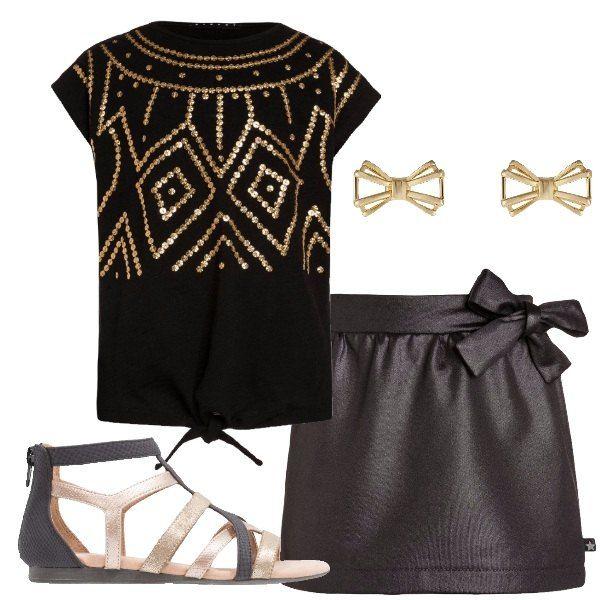 Outfit adatto ad una ragazzina composto da gonna corta con fiocco in vita, maglia a maniche corte con applicazioni dorate e fiocco sul fondo, scarpe basse nere e dorate e orecchini a forma di fiocco.