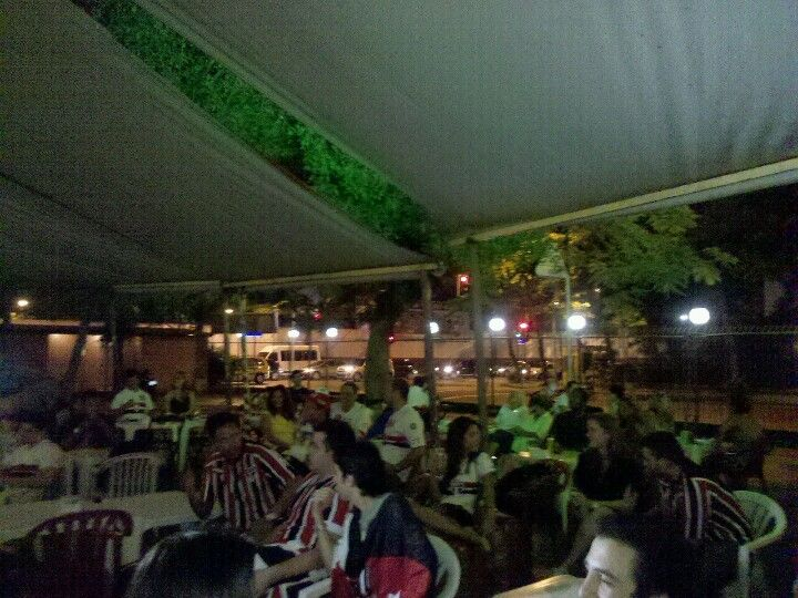 Fans gather round the outdoor screen at this Rio covered market-turned biergarten at night. Find more best places to watch the World Cup in Brazil:http://pin.it/V6SKWXH