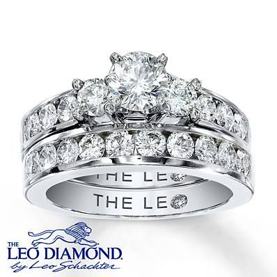 The center of this eye-catching engagement ring features a trio of Leo Diamonds with additional round Leo Diamonds that flow along the 14K white gold band. The matching wedding band features a dazzling array of round Leo Diamonds. This diamond bridal set has a total diamond weight of 2 carats and is independently certified. The center diamond is laser-inscribed with a unique Gemscribe® serial number.