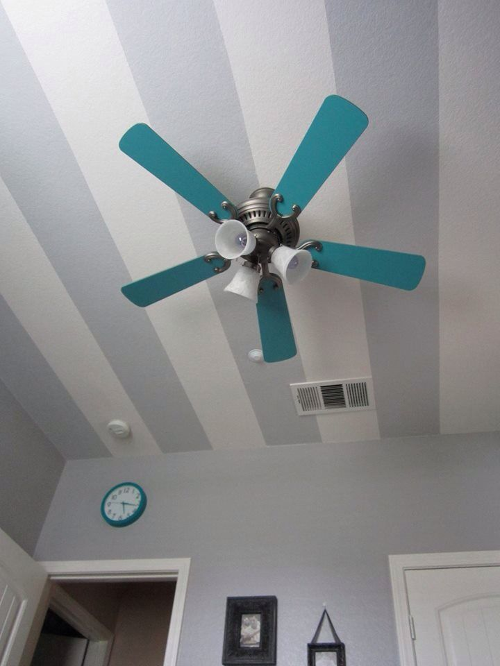 Grey chevron and teal or turquoise boys' nursery or room with black furniture. Pained ceiling fan and striped ceiling.