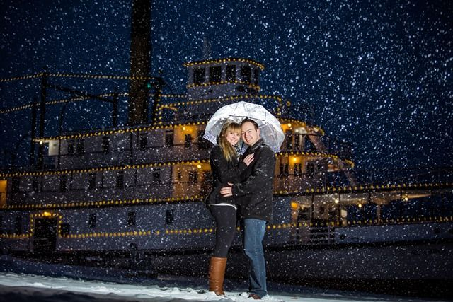 Moments Under Frame - Winter Engagement Photo Shoot - Background Stern Wheeler SS Sicamous lit up at night, with dusting of snow. Find the ship just beside the beach in Penticton (Okanagan, BC, Canada).