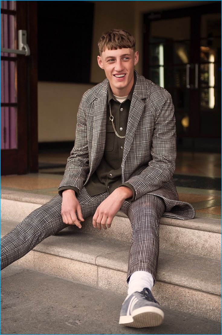 All smiles, Aubrey wears a coat and pants by COS with a Kenzo x H&M shirt, River Island t-shirt, Topman necklace, Calzedonia socks, and Adidas Gazelle sneakers.