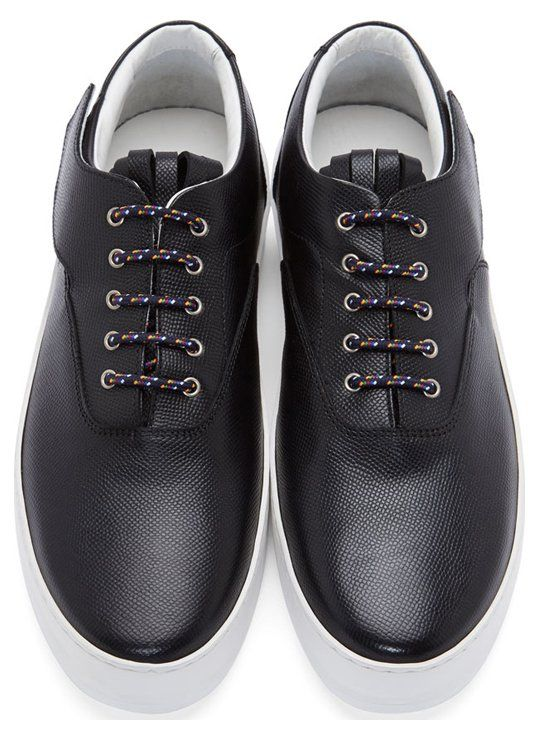 "Black Leather Fringed Platform Sneakers by Krisvanassche. Low-top pebbled leather sneakers in black. Round toe. Multicolor laces in oxford-style lace-up closure. Fringe detail at tongue. Velcroed ""wing"" detail at side collar. Platform sole in white. Tonal stitching. Approx. 1.5"" platform. Upper & lining: leather. Sole: rubber. Made in Italy. http://www.zocko.com/z/JEoiw"