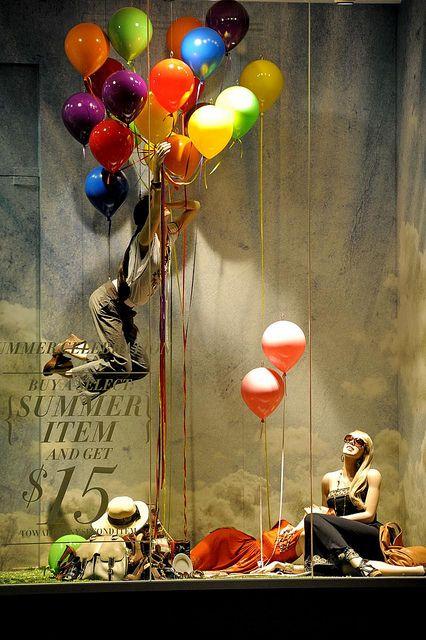 I love this display and think its very creative with loads of multi-coloured balloons holding a mannequin up.