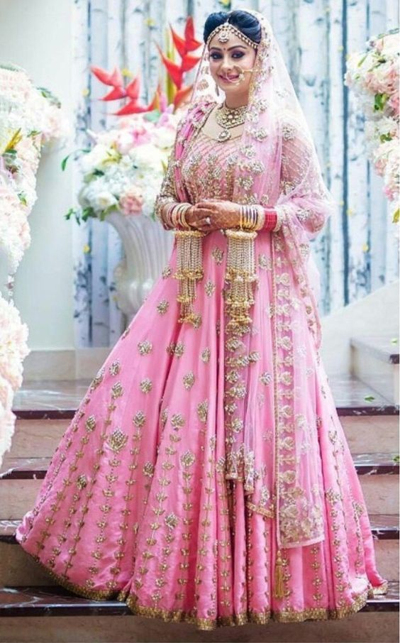 Absolutely love this brides wedding look | Pink lehenga with golden zardosi detailind | Love her kaleere with pearl chains and jhumkis | Indian bridal loook inspiration | Stunning Indian brides | Pastel bride | Image source: Pinterest | Every Indian bride's Fav. Wedding E-magazine to read. Here for any marriage advice you need | www.wittyvows.com shares things no one tells brides, covers real weddings, ideas, inspirations, design trends and the right vendors, candid photographers etc.