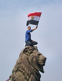 2011, Arab Spring: A protester holds an Egyptian flag during the protests that started on January 25 in Egypt.