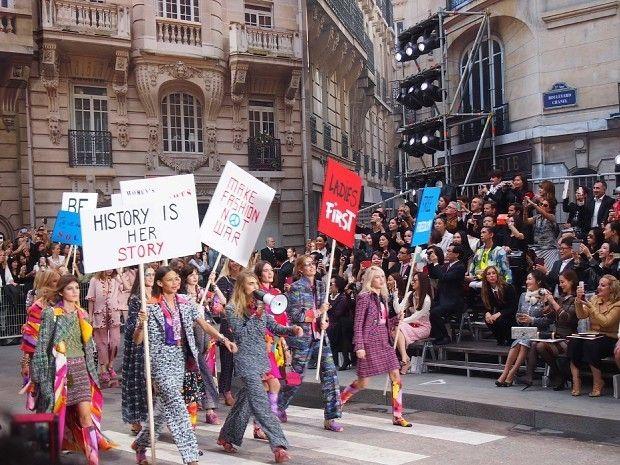 プラカードを掲げ、デモ行進のように練り歩くモデルたち。背景は本物ではなく、芝居で使われる書き割り=永田晶子撮影