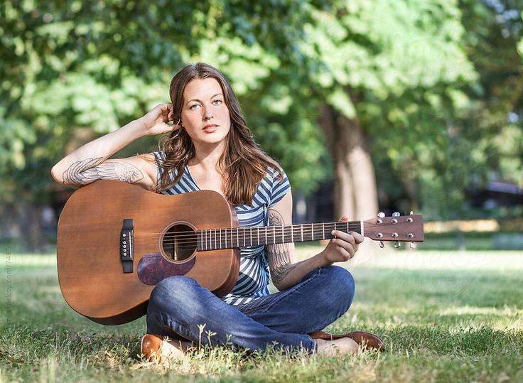 Attractive Caucasian woman sitting cross-legged in a park with her guitar in her lap.