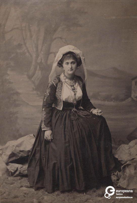 B/W photo of a woman with local costume from Corfu. Creator: Studio B.Borri Date: 1880 Institution: Peloponnesian Folklore Foundation Provider: Europeana Fashion