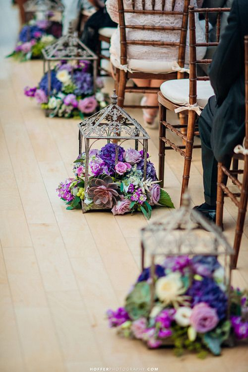 Wedding aisle decor. Fresh cut flowers and succulents arranged in iron terrarium lanterns. Flowers in lavender, white, purple, blue, and fuchsia. Floral Design: www.papertini.com Photography: www.hofferphotography.com