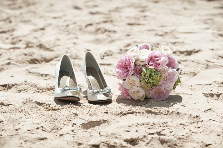 wedding shoes and flowers on the beach