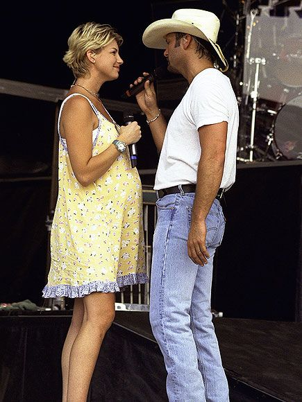 "Tim & Faith: 18 Years in Adorable Photos | TRAVELING TWO | The singers were inseparable during a July 1998 performance at Jamboree in Morristown, Ohio. They even named their tour bus at the time the Love Bus, because ""a lot goes on in that bus,"" admitted Hill. Apparently: Daughter Maggie was born in 1998, too."