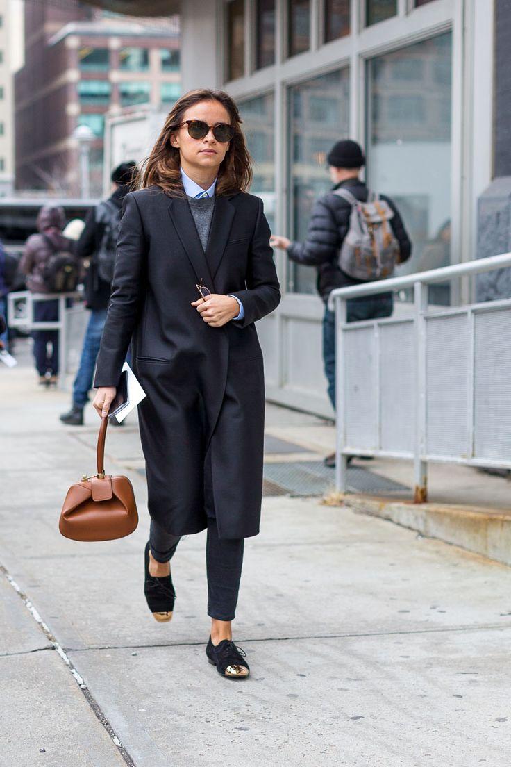 Miroslava Duma | long black blazer coat + black pants + gray sweater + blue button down + black gold capped oxfords + tan handbag