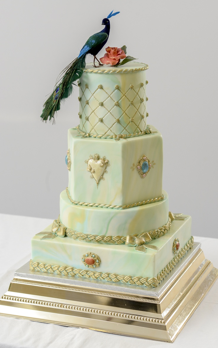 This cake is a work of art in its construction. Not only did we have three different shapes; square, round and hexagonal, but we were also trying to pattern match the marbling on all four tiers. The colours used for the marbling are white, umber yellow, sky blue and aqua green. The cake is then finished off with embellishments like jewellery, ropes, bows and sugar flowers. http://www.facebook.com/pages/Dita-Lee-Cakes/519935201363767