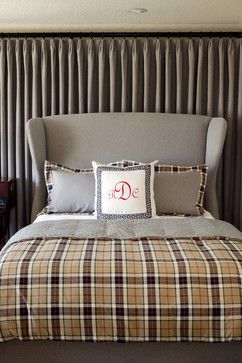 A neutral, monochromatic modern upholstered wing bed dressed with Euro Shams with Plaid only on the flanges and a coordinating throw at the foot of the bed in guestrooms is a nice ode to Tartan. -Tobi Fairley Interior Design