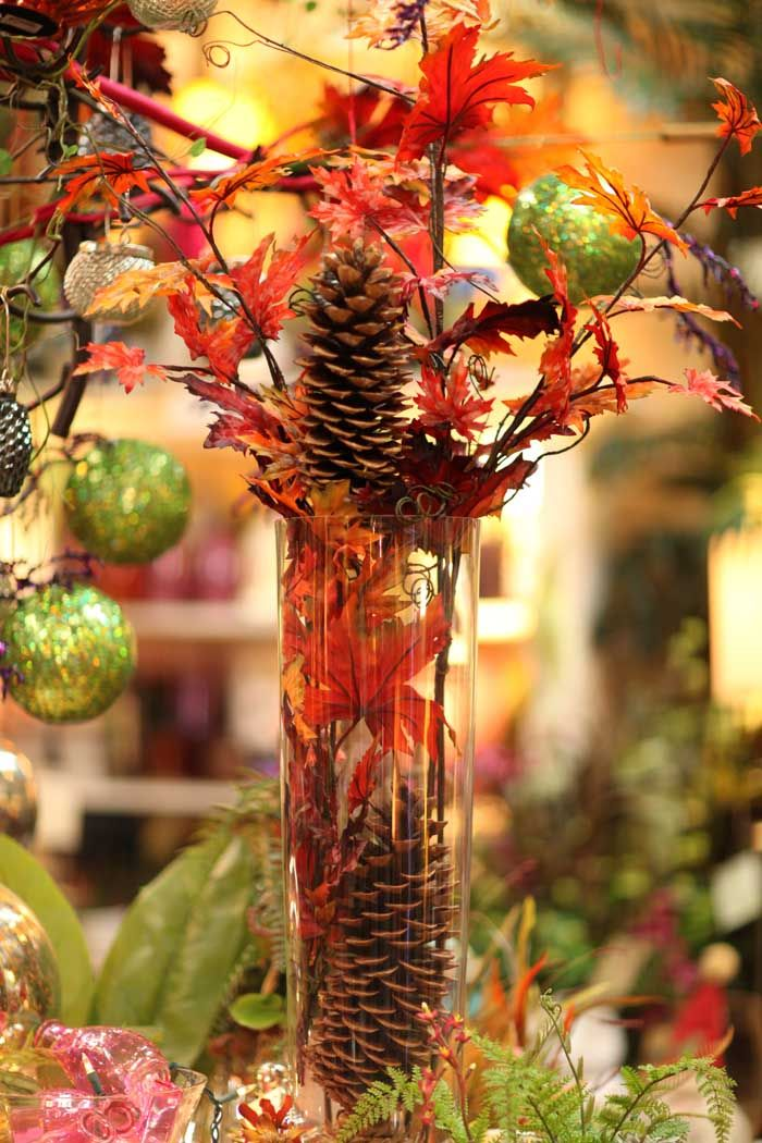 Tall glass vase with pine cones and fall foliage leaves