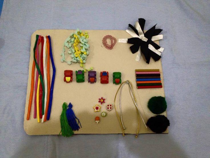 6 MESES - Placa sensorial, feita de papelão, e objetos de texturas diferentes (bexigas, pompons, imã de geladeira)