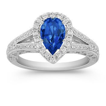 Pear Shaped Halo Diamond Engagement Ring with Pave Setting. Displayed with a pear shaped blue sapphire. Available with your choice of sapphire, diamond or ruby.