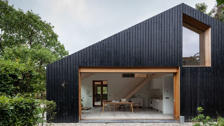 Workshop Architecten has created a blackened wood barn for a farm in the Netherlands, which is divided into separate living quarters for sheep and people