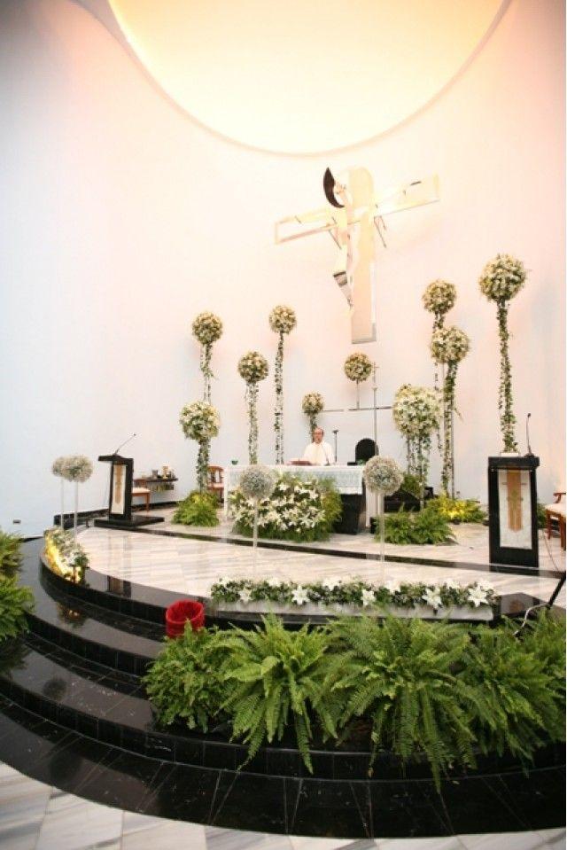 Lindo altar que luce toda la decoración con topiaris a diferentes alturas colocados en bases de acrílicos, jardineras en las escaleras con un toque de flor.