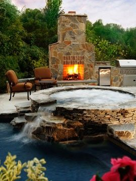 Out door fireplace and hot tub that falls into pool.
