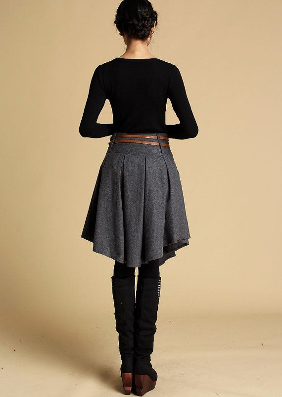 Show off you individuality with this dark gray wool mini skirt. Custom handmade from a soft wool blend, this designer mini skirt features a stylish wide waist band and trendy pleats. Ideal for the office or even a leisurely shop excursion, you'll look sophisticated each time you wear it. Pair it with a fitted turtleneck and knee length boots for a look that impresses. It will make an alluring addition to you winter wardrobe. It also makes a magical gift idea for a sister or mother. It is a…