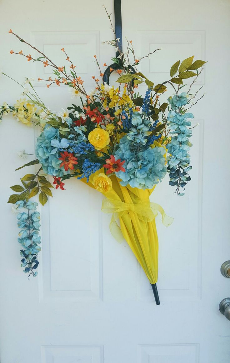 DIY Umbrella Wreath  Yellow umbrella with an assortment of blue, yellow, orange and white silk flowers. Perfect for spring