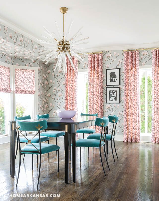 """A local decorator helps a Little Rock family transform a traditional house into a fun, funky place to call home   Modern Mix   At Home in Arkansas   January/February 2017   Osborne and Little wallpaper in the dining room has a """"bold and whimsical"""" magnolia blossom motif. The drapery fabric is Schumacher, chairs are by Jonathan Adler, and the light is from Arteriors. The Baker dining table is a family heirloom, which Kidd had painted.   Dining Room"""