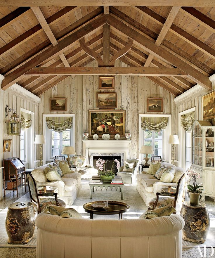 In Nancy and Bill Morton's Florida home, the living room's pecky-cypress paneling was lightened by decorative painter Bob Christian, whose work can also be seen on the tile fireplace surround. The landscape paintings are 19th-century English, the roll-arm sofas are by O. Henry House, and the Louis XV–style armchairs by Edward Ferrell + Lewis Mittman, in the foreground, are upholstered in a Brunschwig & Fils floral.
