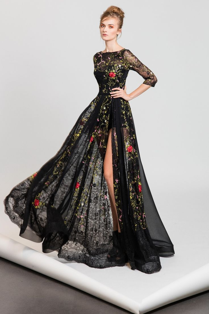 Black evening dress with bateau neckline in embroidered lace featuring a floral pattern, a belt on the waist and a side slit.