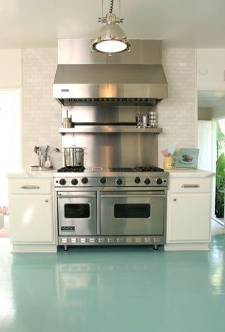 Beach house kitchen with turquoise high gloss painted wood floor, stainless appliances, nickle pendant light and a white subway tile backspl...