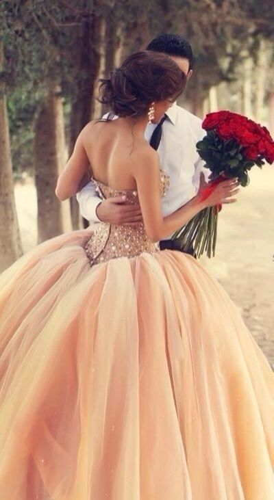 Flattering peach gown, wonderfully set off by the red bouquet.