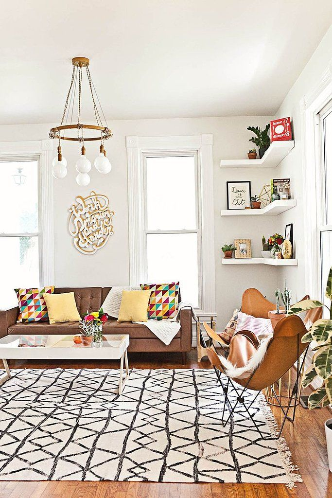 Everything about this sitting room: printed rug, elegant chandelier, and leather butterfly chair