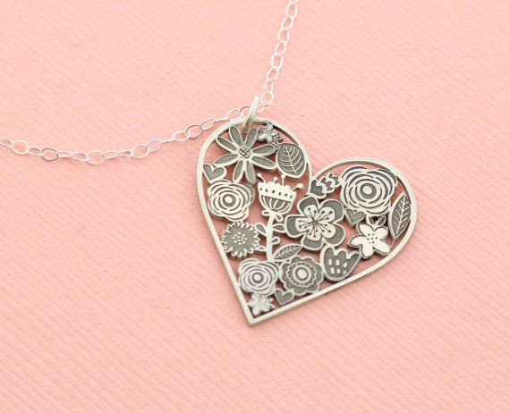 """Valentine's Day Gift Idea - Heart Flower Necklace! An intricate cutout heart necklace with a pretty floral design. The necklace is made of solid sterling silver and handcrafted in our studio. Each charm is about 1 inch in diameter and hangs from a 16"""" cable chain. #valentinesdaygiftideas #valentinesday #necklace #jewelry #heart #flowers #ad"""