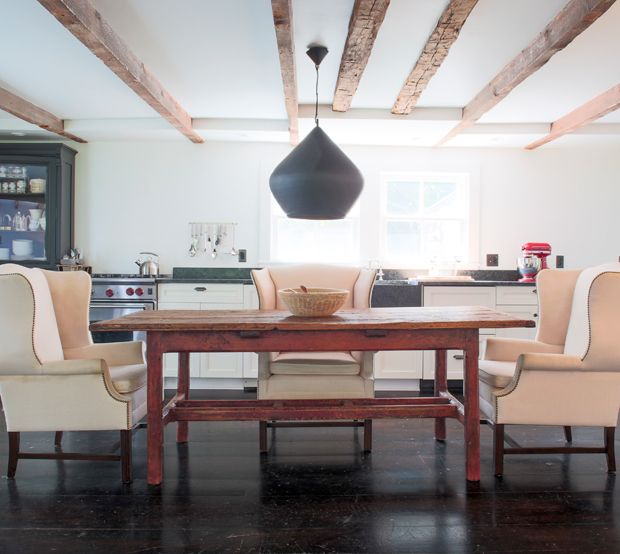 In this Shelter Island, N.Y., vacation home, a mod oversized pendant by Tom Dixon contrasts beautifully with weathered beams and an Irish farmhouse table. Handsome cream wingback chairs are a fresh ch