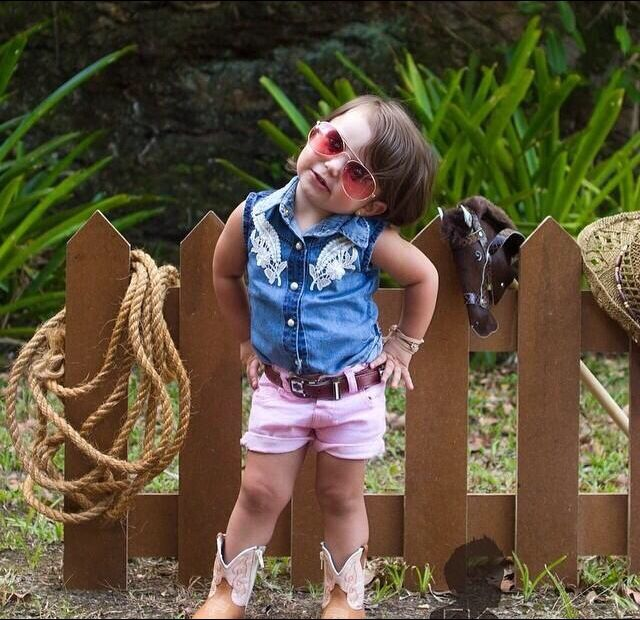 Little Girl In Cowgirl Outfit And Wearing Sunglasses