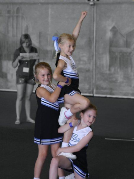 KNEE STAND: Lowest level of single-leg stunt, usually performed in Level 1 Mini and Youth cheerleading where the base kneels with one leg at a 90 degree angle and the flyer steps up in liberty position with the aid of a backspot. #Cheerleading #Cheer #Stunt #CheerWordOfTheWeek #Level1 #Youth #Mini