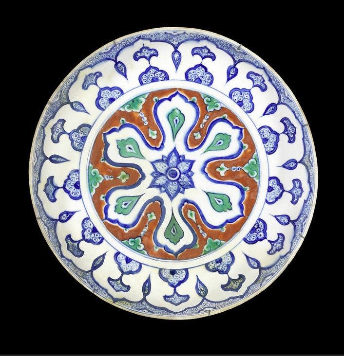 A rimless polychrome Iznik pottery Dish Turkey, circa 1590 decorated to centre with a cobalt flower within a six-lobed rosette on a red ground with green cloud detail, the walls with a further series of cobalt-blue arched elements on a ground of dense scrollwork, with brown label in the form of a flower to reverse, no. 41 approx. 30cm. diam.