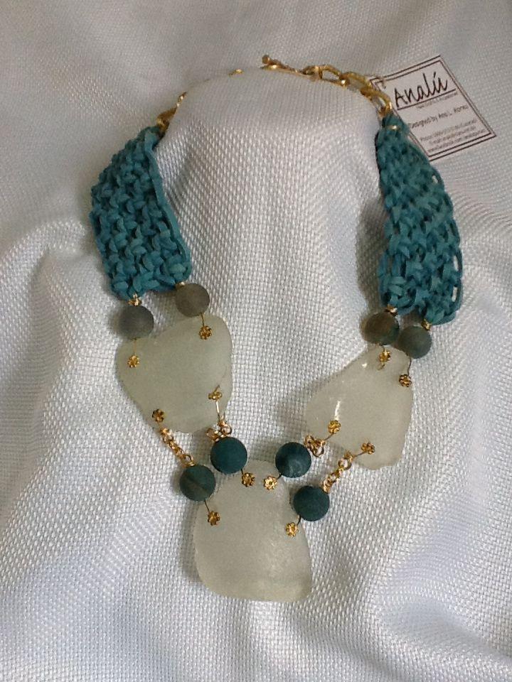 Collar corto hecho con gamuza azul tejida en nudos de macrame y piezas de Sea glass blanco, bolas de cristal opaco y terminaciones en dorado.