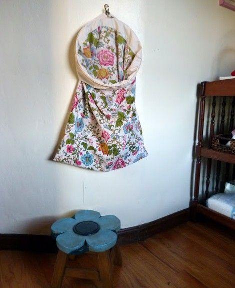 Deze kleurrijke kussensloop doet dienst als wasmand. Zo heb je alle vuile was binnen handbereik. Met metaaldraad kun je een opening maken, zodat je de was er gemakkelijk in kunt gooien en door een ring te bevestigen, kun je de wasmand ophangen aan de muur.