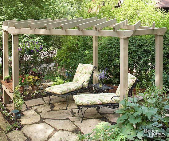 When you build a pergola, consider positioning it at an angle for added interest. Although it occupies a flagstone patio with a square outline, this pergola was deliberately designed as a corner structure. The clipped front corner creates a wide diagonal entry that offers access to both the adjacent house and a terraced landscape nearby./