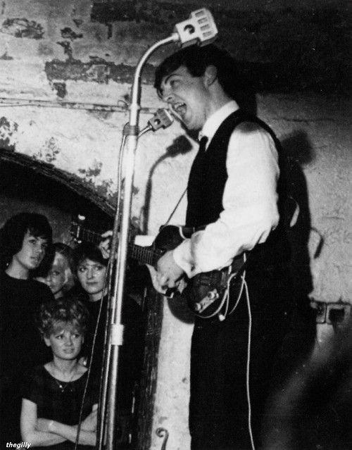 "Paul McCartney and Bernadette Farrell- Byrne (performing at the Cavern with the Beatles, late 1962. The young woman sitting down is Bernadette Byrne (maiden name Farrell). She was George Harrison's girlfriend for a time and went on to co-found The Beatles Story museum in Liverpool.  Scanned from ""The McCartneys: In the Town Where They Were Born"" by Kevin Roach.)"