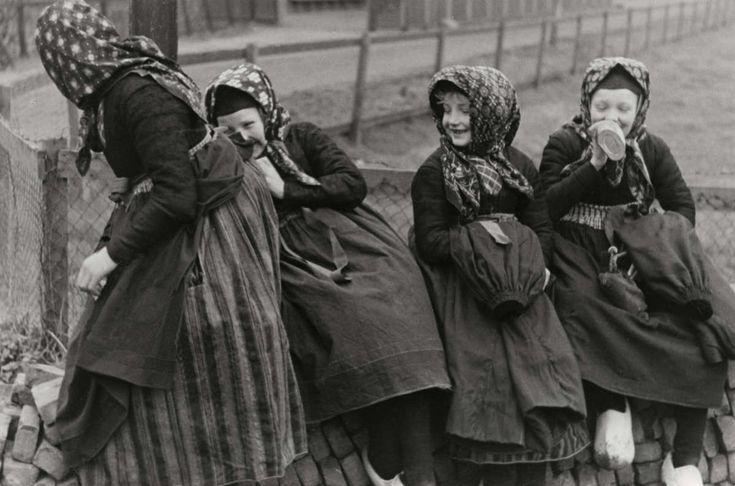 Steden en dorpen. Vier kleine meisjes verbergen zich lachend voor de fotograaf. Staphorst, Nederland, 1937.
